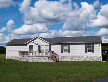 Gray trailer home with stone foundation or skirting and shutters in front of a beautiful sky.