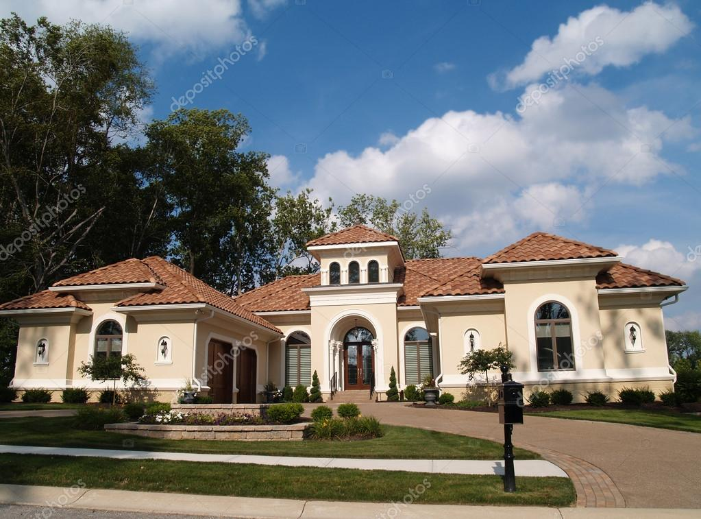 One Story Stucco Residential Home With A Red Clay Tile Roof And Side Garage