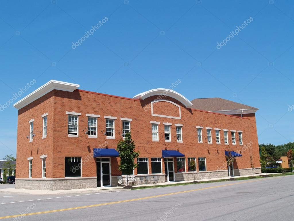 Small two story, new, brick store front with blue awnings along a street with plenty of copy space.