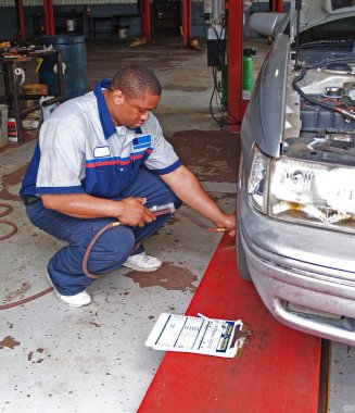 Auto mechanic inspecting a cars tire pressure in a service garage.