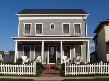 New two story vinyl home built to look like an old historical house with gray vinyl siding and large front porch.