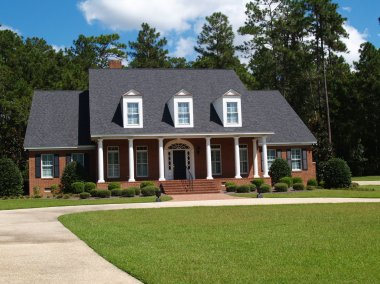 Two story brick residential home with large front porch and side entrance garage.