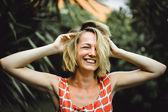 Fotografie blond holka proti tropické palmy