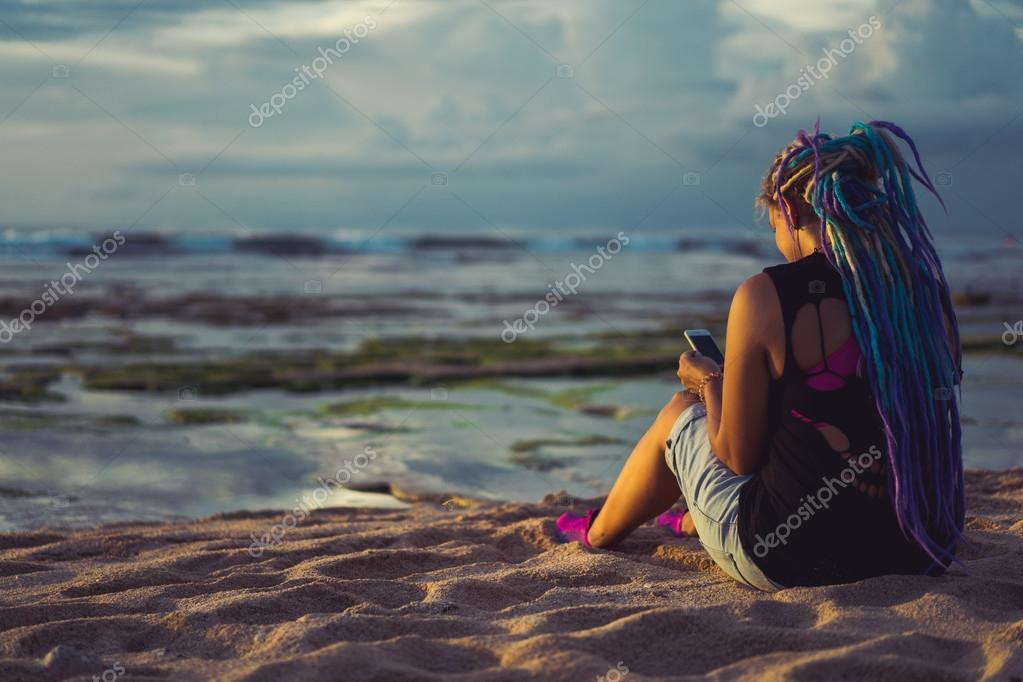 hipster woman on the beach watching the sunset