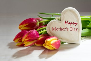 Fresh red orange tulips and a wooden heart, love decoration text happy mother's day