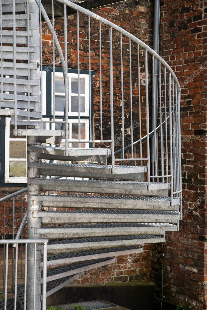 modern exterior spiral staircase of metal on an old brick building ...