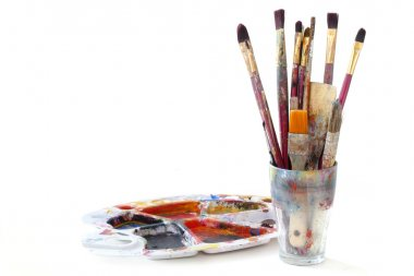 Paint brushes in a glass and used pallete with colors, isolated