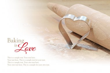 baking background, heart cookie cutter and rolling pin, blurred