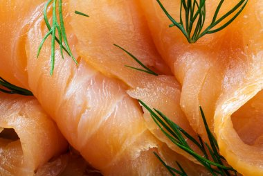 close up of smoked salmon with dill garnish, food background