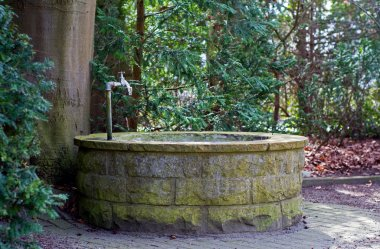 round water well  with faucet in a cemetery with old trees