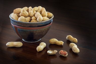 peanuts in a ceramic bowl on a dark brown table, copyspace