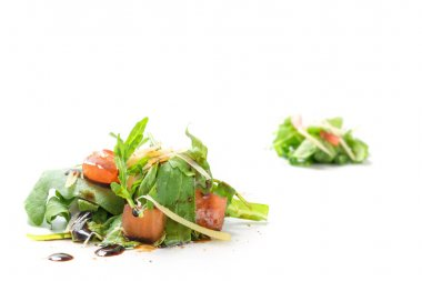small heaps of rucola salad with tomatoes and  parmesan isolated