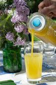 férfi kezét narancs gyümölcslé ömlött egy üveg, a nyári ga