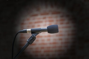 microphone in front of an old blurred brick wall with a light sp