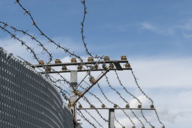 High Security Fence with electric barbed wire against a blue sky