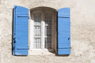 old window with blue shutters and lace curtain in a rough-plaste