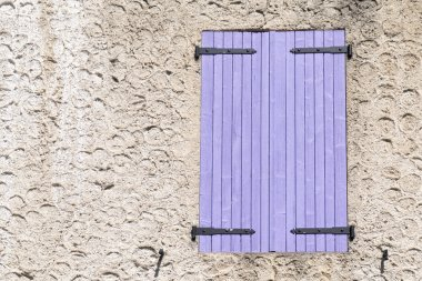 closed window shutters of purple wood in a rough-plastered wall