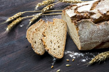 rustic loaf of bread and slices with wheat on dark wood
