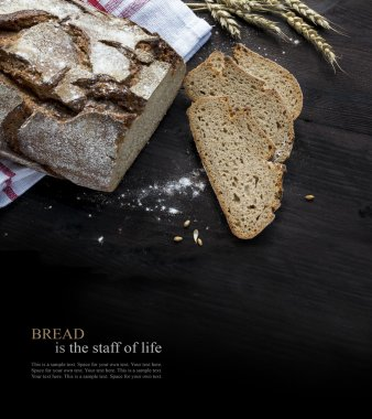 Rustic bread and slices on dark wood fading to black, sample text