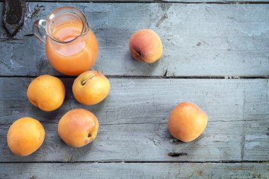 fresh apricots and juice in a glass jug on  rustic gray-blue woo