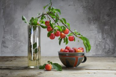 wild red plums on a branch and in a pottery bowl on an old woode