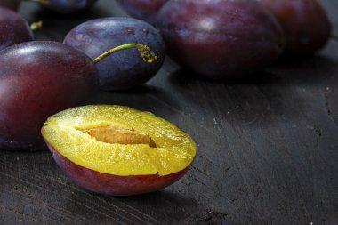 purple plums whole and half on dark brown wood, closeup