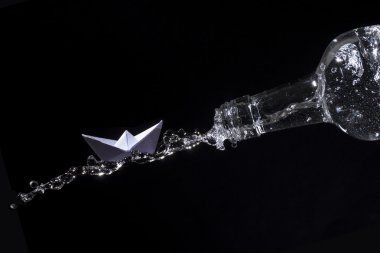 Paper boat rides on a water splash out of a bottle against black