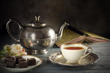 tea in a porcelain cup, old fashioned silver teapot, chocolate c