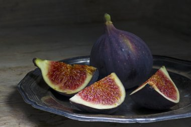 figs on an old silver plate on a rustic wood, dark background