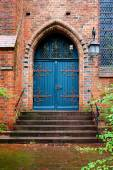 Photo blue wooden door, entrance to an old brick church
