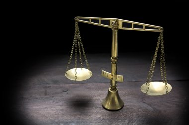 Vintage brass scales of justice in spotlight against a black bac