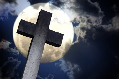 stone cross against the moon, dramatic clouds in the night sky