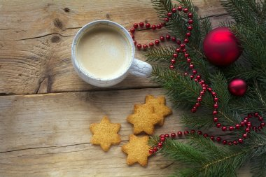 Cup of coffee with cookies in star shape and fir branches with c