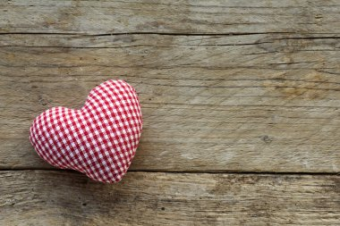 cloth heart with red white pattern on rustic old wood