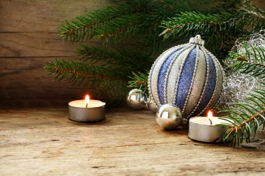 silver and blue baubles, fir branches and candles as Christmas d