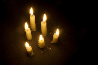 six burning candles on black, view from above, copy space