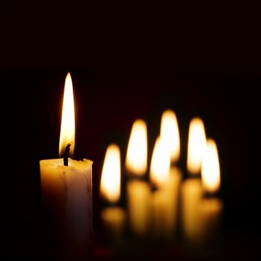 single burning candle and a group of other candles blurred in th