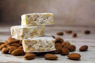 Torrone or nougat and almonds on a rustic wooden table, close up