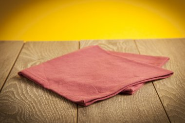 Retro background with wooden table and napkin over yellow rough wall