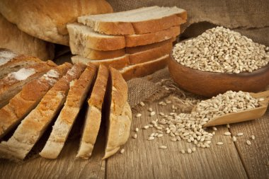 Wheat Bread, wheat seeds and bread slices with wooden background