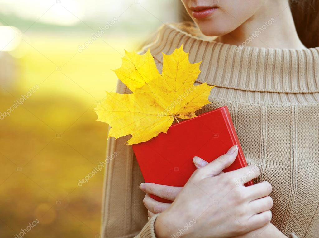 Autumn season, people and reading concept. Woman with book in wa