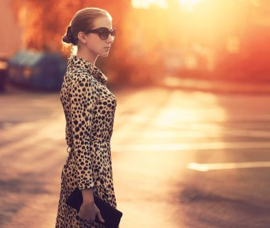 Street fashion, stylish woman in a dress with leopard print, eve