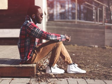 Lifestyle fashion portrait of stylish young african man listens