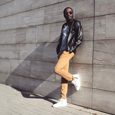 Street fashion, stylish young african man wearing a sunglasses a