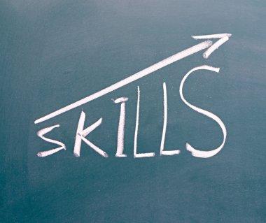 word Skills hand written on the chalkboard with rising arrow gra