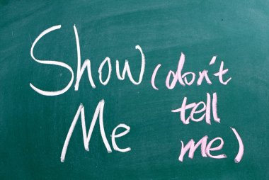 Show Me, Don't Tell Me written by hand on a used blackboard