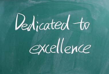 Dedicated to excellence sign on blackboard