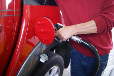 car refueling. hand of a man refuleing a car with petrol in a filling station