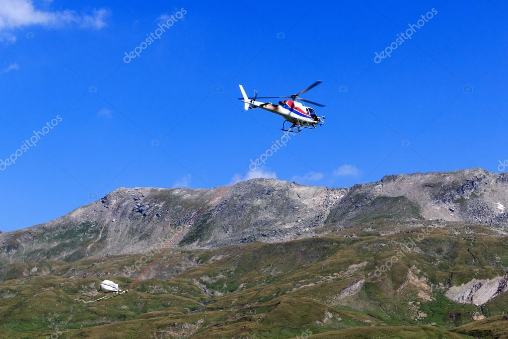 Transport helicopter flying with supplies and mountain panorama in Hohe Tauern Alps, Austria