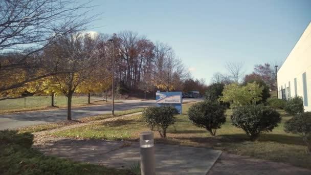 Clarksburg, MD 11 / 08 / 2020: Schwenkaufnahmen einer Außenstelle des United States Postal Service in Maryland. Auf der Eingangstür prangt ein großes USPS-Adler-Logo. Es ist ein sonniger Herbsttag